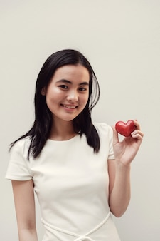 Asian young woman holding red heart, health insurance, donation concept