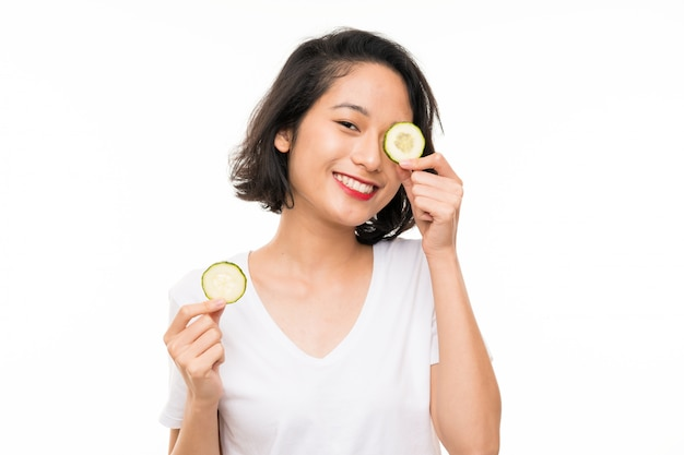 Asian young woman holding slices of cucumber