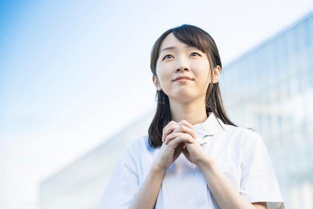 Азиатская молодая женщина в белом халате в позе молитвы
