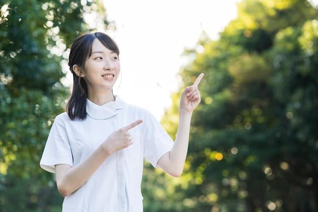 Азиатская молодая женщина в одежде медсестры и позирует с руками