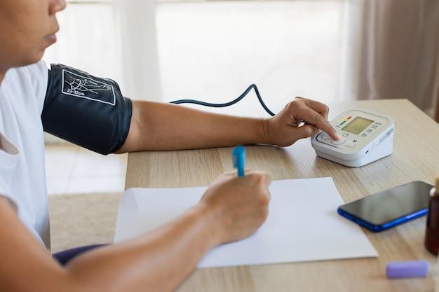 아시아 젊은 여성이 디지털 압력계로 혈압과 심박수를 직접 확인하고 집에서 종이에 기록하고 있습니다. 건강 및 의료 개념입니다.