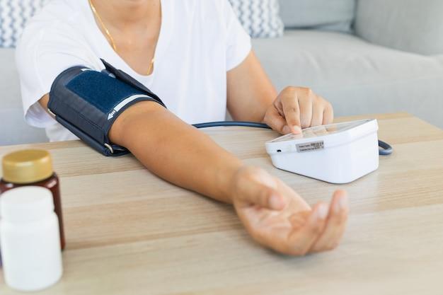 아시아 젊은 여성이 집에서 혼자 디지털 압력계로 혈압과 심박수를 확인하고 있습니다. 건강 및 의료 개념입니다.