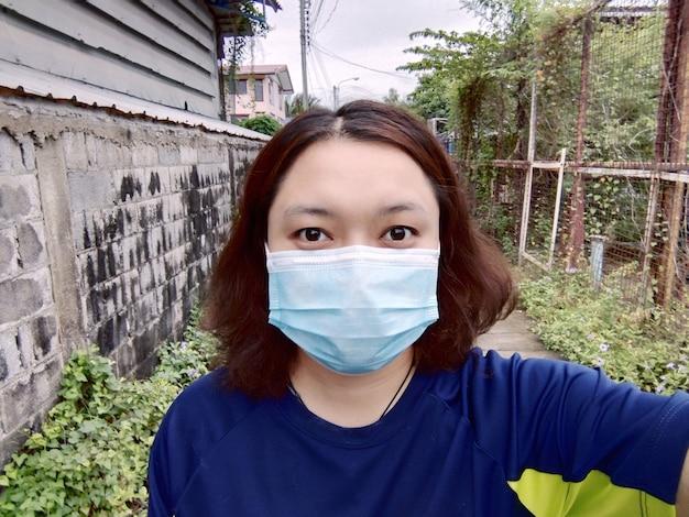 아시아 젊은 여성이 태국에서 많이 퍼지고 있는 코비드-19를 예방하고 보호하기 위해 마스크를 쓰고 있습니다. 그녀는 집에서 격리하고 일하는 동안 스마트폰으로 셀카를 찍는다. 잠금에 대한 새로운 표준.
