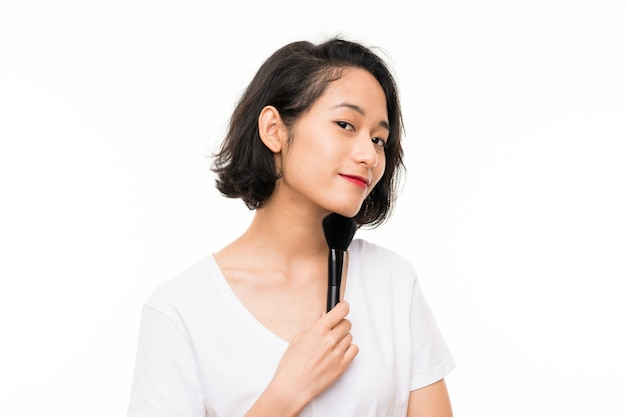 Asian young woman over isolated background with makeup brush