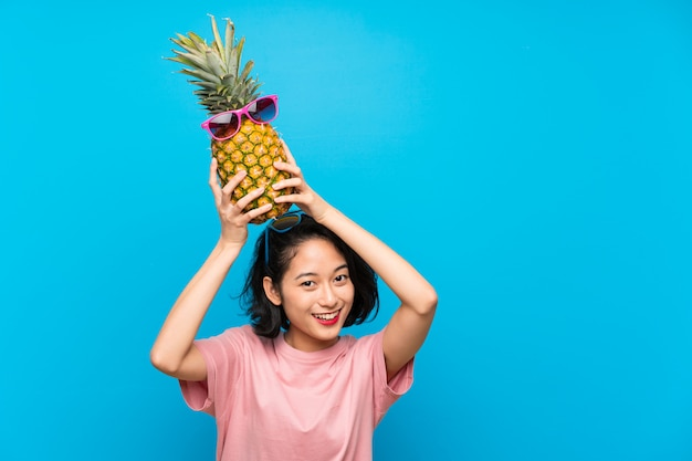 Asian young woman over isolated blue background holding a pineapple with sunglasses
