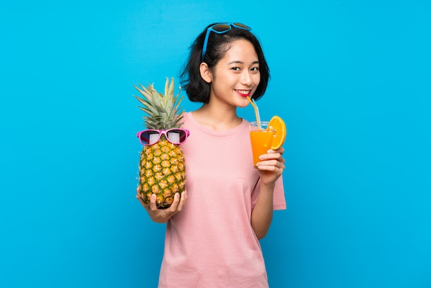 Asian young woman over isolated blue wall holding a pineapple with sunglasses