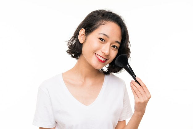 Asian young woman over isolated wall with makeup brush