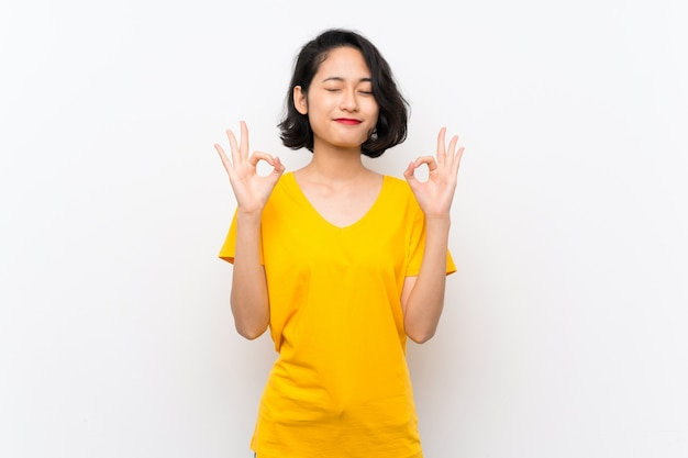 Asian young woman over isolated white background in zen pose