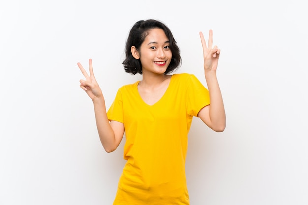 Asian young woman over isolated white  showing victory sign with both hands