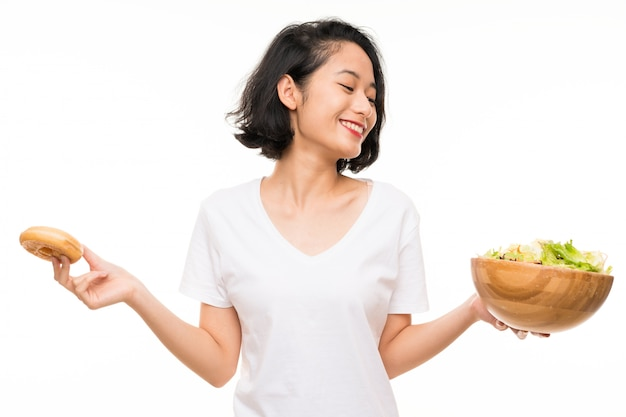 Asian young woman over isolated  with salad and donut