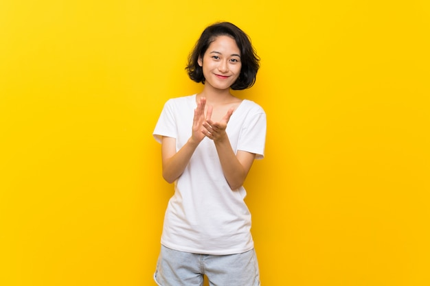 Asian young woman over isolated yellow wall applauding after presentation in a conference
