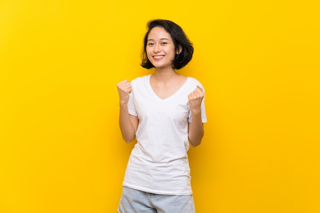 Asian young woman over isolated yellow wall celebrating a victory in winner position
