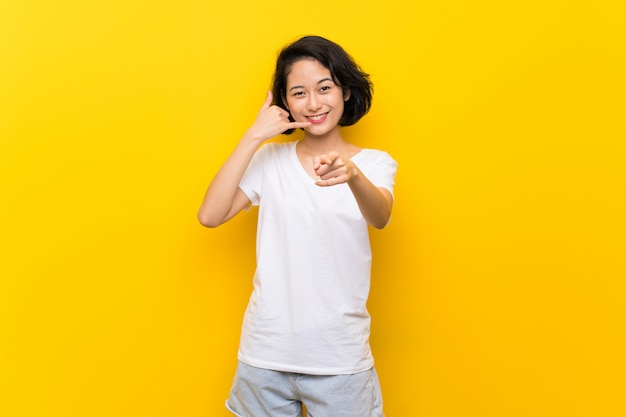 Asian young woman over isolated yellow wall making phone gesture and pointing front