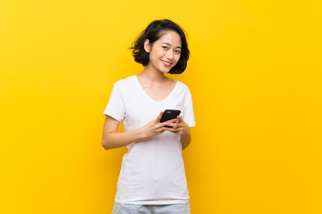 Asian young woman over isolated yellow wall sending a message with the mobile