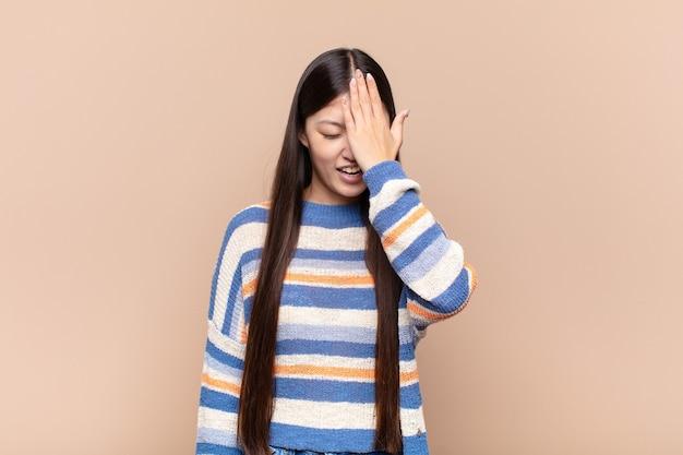笑って額を叩くアジアの若い女性は、d'oh!私は忘れたか、それは愚かな間違いでした