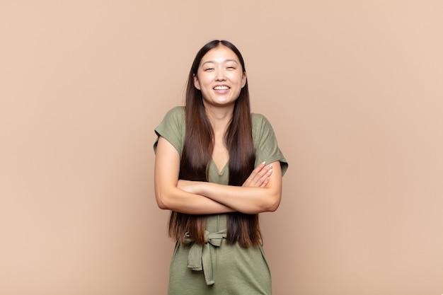 孤立した腕を組んで幸せに笑うアジアの若い女性