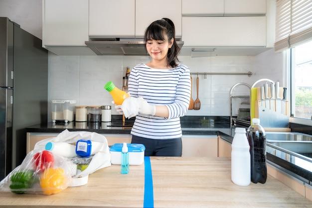 アジアの若い女性が食料品を分割されたテーブルにレイアウトし、拭く
