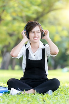 Asian young woman listening music from mp3  player in summer park.
