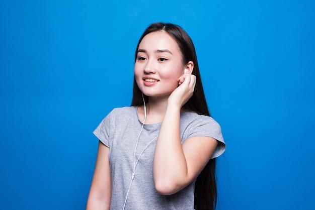 Азиатская молодая женщина слушает аудиокнигу через наушники на синей стене