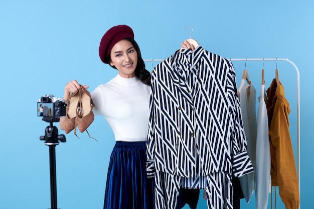 Молодая азиатская женщина в прямом эфире продает модную одежду, которую блогер представляет для социальных сетей. она является влиятельным лицом в социальных сетях.
