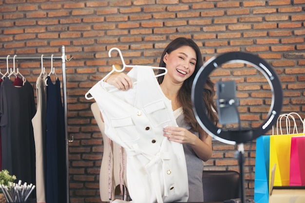 Asian young woman live streaming for sale fashion clothing is blogger presenting for social people. her is influencer in social online.