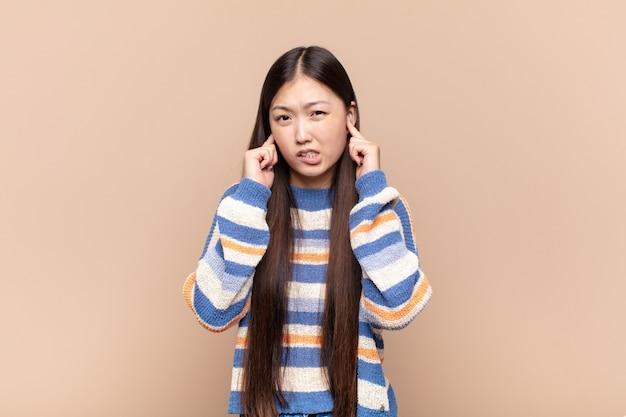 怒り、ストレス、イライラしているように見えるアジアの若い女性は、耳をつんざくような音、音、または大音量の音楽で両耳を覆っています
