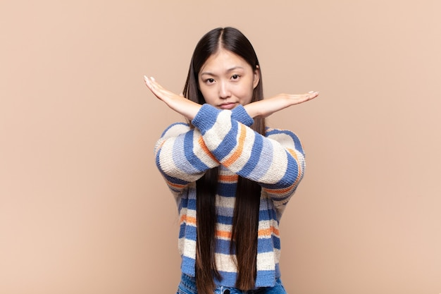 Asian young woman looking annoyed and sick of your attitude, saying enough! hands crossed up front, telling you to stop