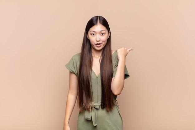 不信に驚いて見えるアジアの若い女性