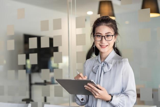 Азиатская молодая женщина. глядя на камеру, держащую планшет в офисе.