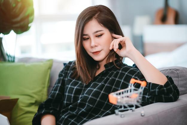 Азиатская молодая женщина смотрит на крошечную корзину и думает, чтобы делать покупки онлайн, оставаясь дома в ситуации вспышки коронавируса