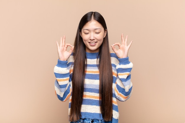 Asian young woman looking concentrated and meditating, feeling satisfied and relaxed, thinking or making a choice