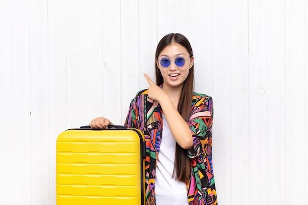 興奮して驚いたアジアの若い女性は、スペースをコピーするために横と上を指しています。休日の概念