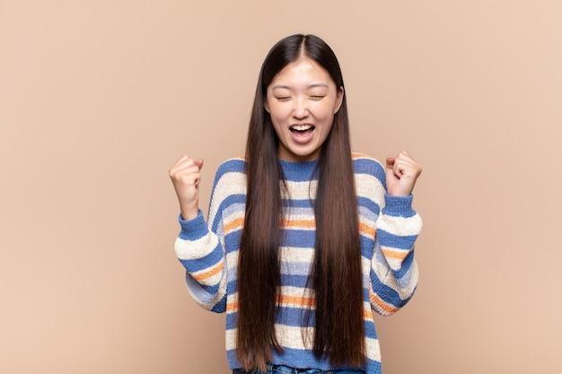 Азиатская молодая женщина выглядит очень счастливой и удивленной