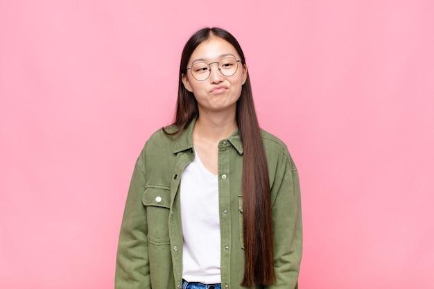Азиатская молодая женщина выглядит глупо и смешно с глупым косоглазым выражением лица, шутит и дурачится