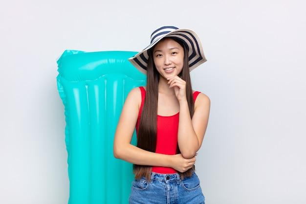 幸せそうに見えて、あごに手を当てて笑っているアジアの若い女性、疑問に思ったり質問したり、オプションを比較