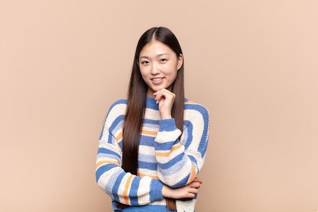 아시아 젊은 여자가 행복을 찾고 턱에 손으로 웃고 궁금하거나 질문