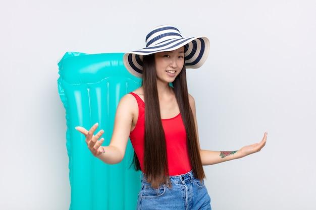 Азиатская молодая женщина выглядит счастливой, высокомерной, гордой и самодовольной, чувствуя себя номером один. летняя концепция