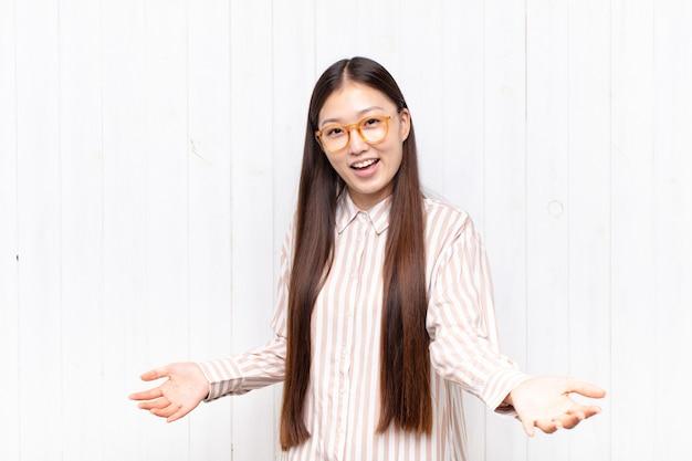 Азиатская молодая женщина выглядит счастливой, высокомерной, гордой и самодовольной изолированной
