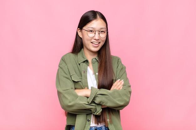 Азиатская молодая женщина выглядит счастливой, гордой и довольной, улыбающейся со скрещенными руками