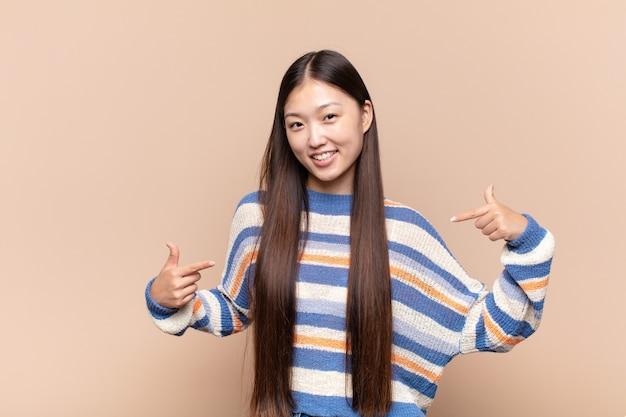 Азиатская молодая женщина выглядит гордой, высокомерной, счастливой, удивленной и удовлетворенной, указывая на себя, чувствуя себя победителем