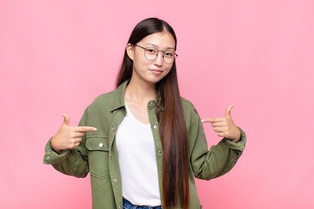 誇らしげに、傲慢で、幸せで、驚き、満足しているアジアの若い女性は、自分を指して、勝者のように感じています