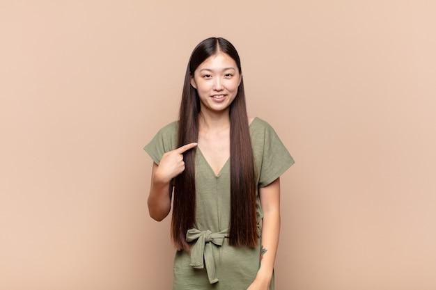 자랑스럽고 자신감 있고 행복하고 웃고 자기를 가리 키거나 번호 하나의 기호를 만드는 아시아 젊은 여자