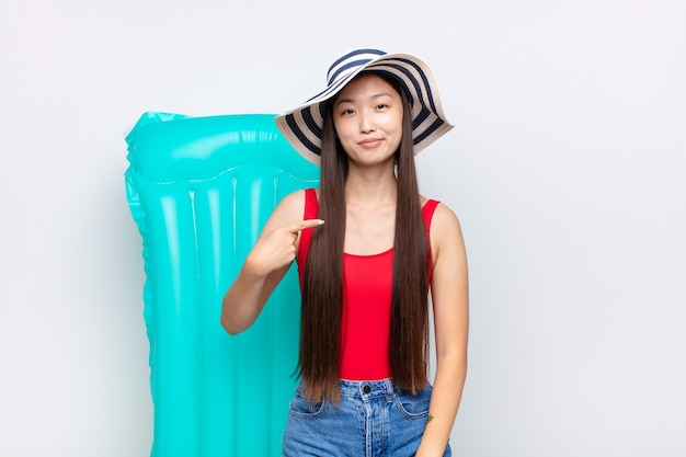 Asian young woman looking proud, confident and happy