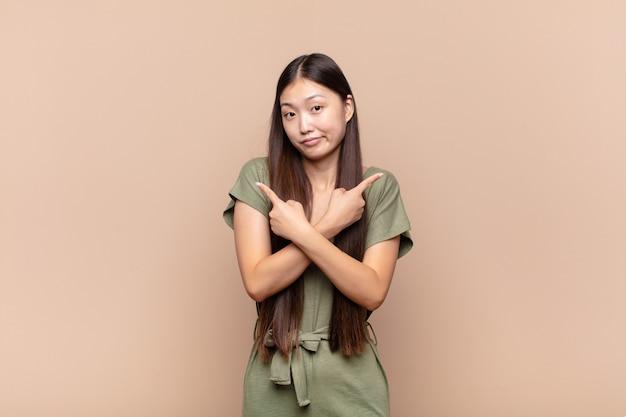 Азиатская молодая женщина выглядит озадаченной и сбитой с толку, неуверенно и с сомнениями указывает в противоположные стороны