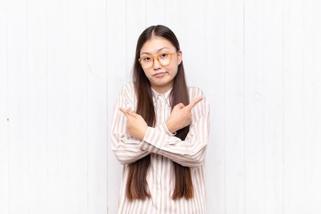 어리둥절하고 혼란스럽고 불안해하며 의심으로 반대 방향을 가리키는 아시아 젊은 여성
