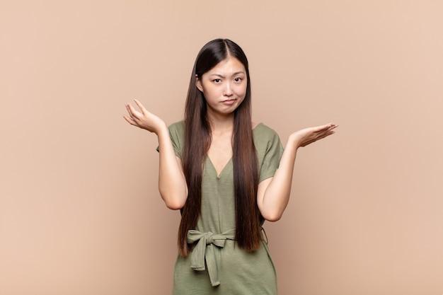 困惑し、混乱し、ストレスを感じ、さまざまな選択肢の間で疑問に思って、不確かに感じているアジアの若い女性