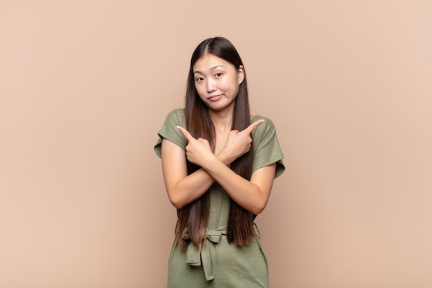 Asian young woman looking puzzled and confused, insecure and pointing in opposite directions with doubts