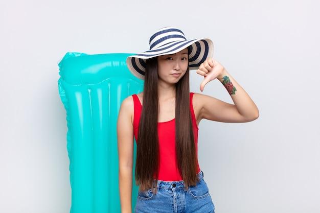 Азиатская молодая женщина выглядит грустной, разочарованной или сердитой, показывая изолированные пальцы