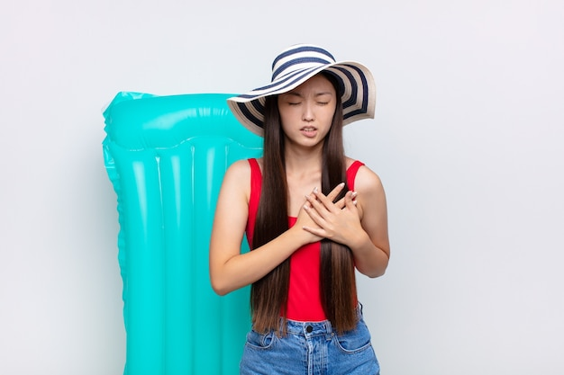 Азиатская молодая женщина выглядит грустной, обиженной и убитой горем, держит обе руки близко к сердцу, плачет и чувствует себя подавленной. летняя концепция