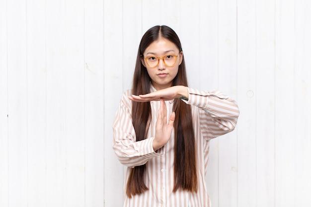 Азиатская молодая женщина выглядит серьезной, суровой, сердитой и недовольной, делая знак тайм-аута